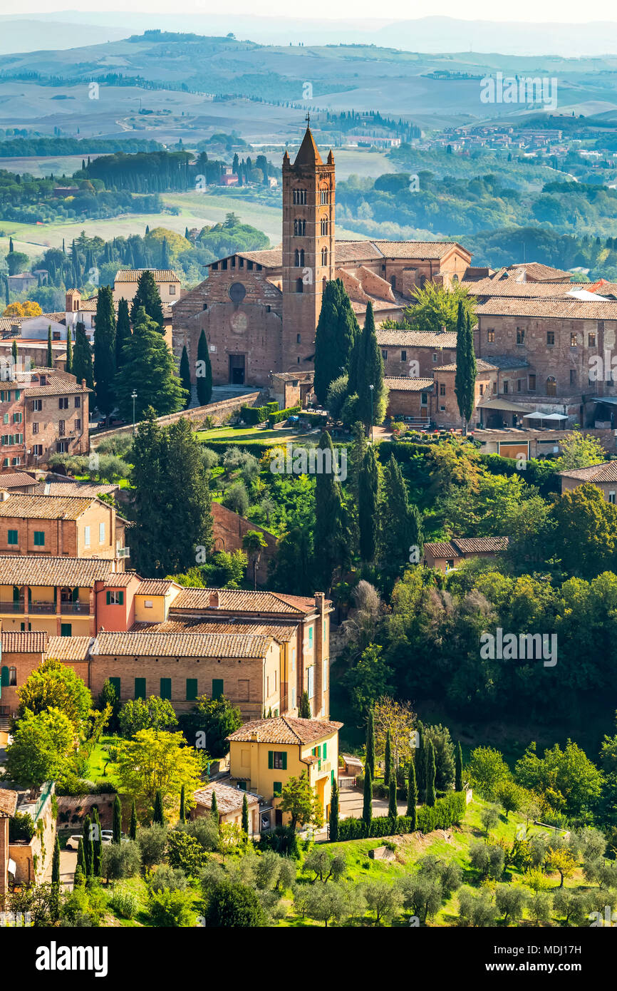 Stone buildings and church on landscape covered with trees and rolling hills in the background; Siena, Tuscany, Italy - Stock Image