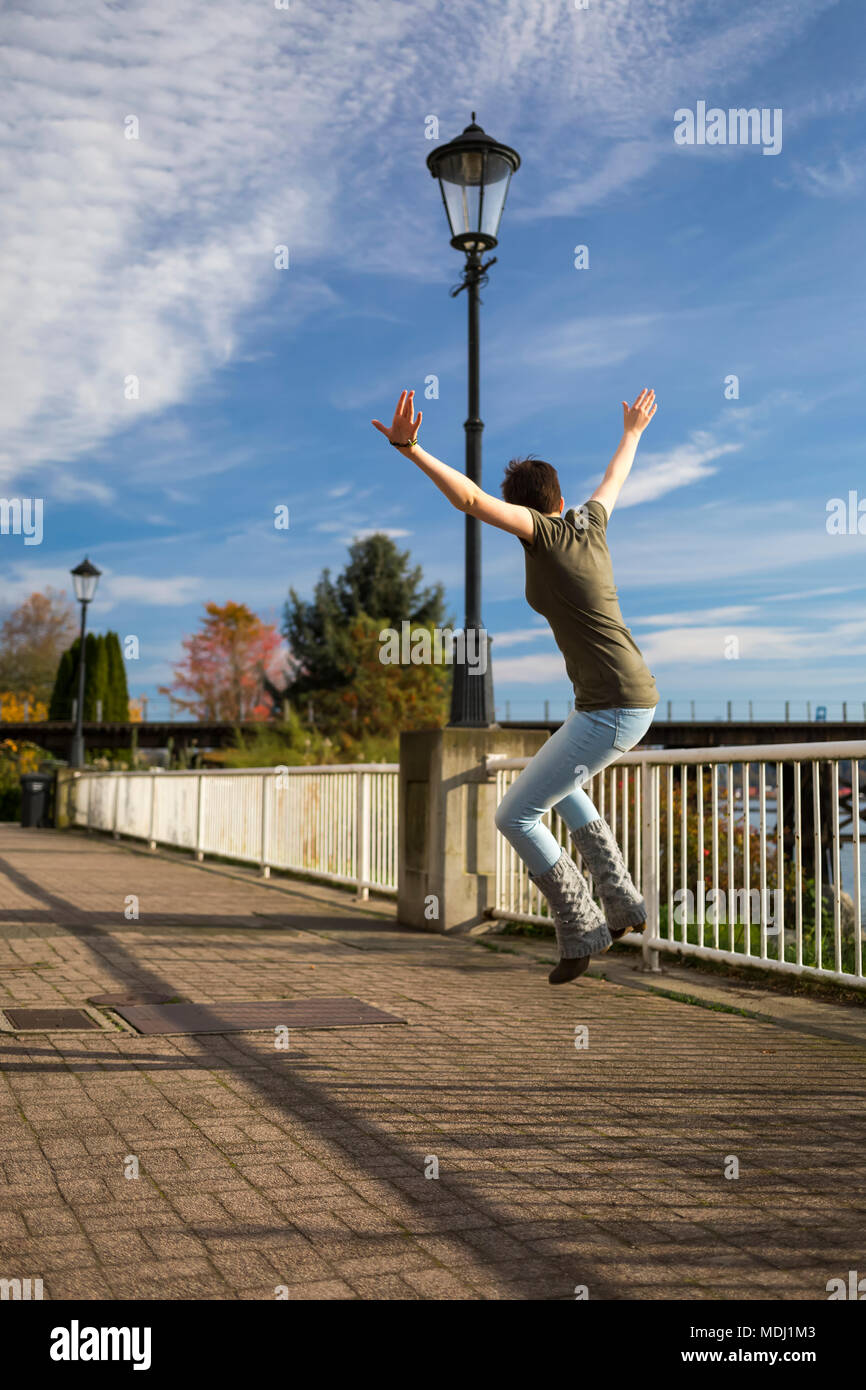 A young woman leaps in the air with arms outstretched on a trail in a park; New Westminster, British Columbia, Canada - Stock Image