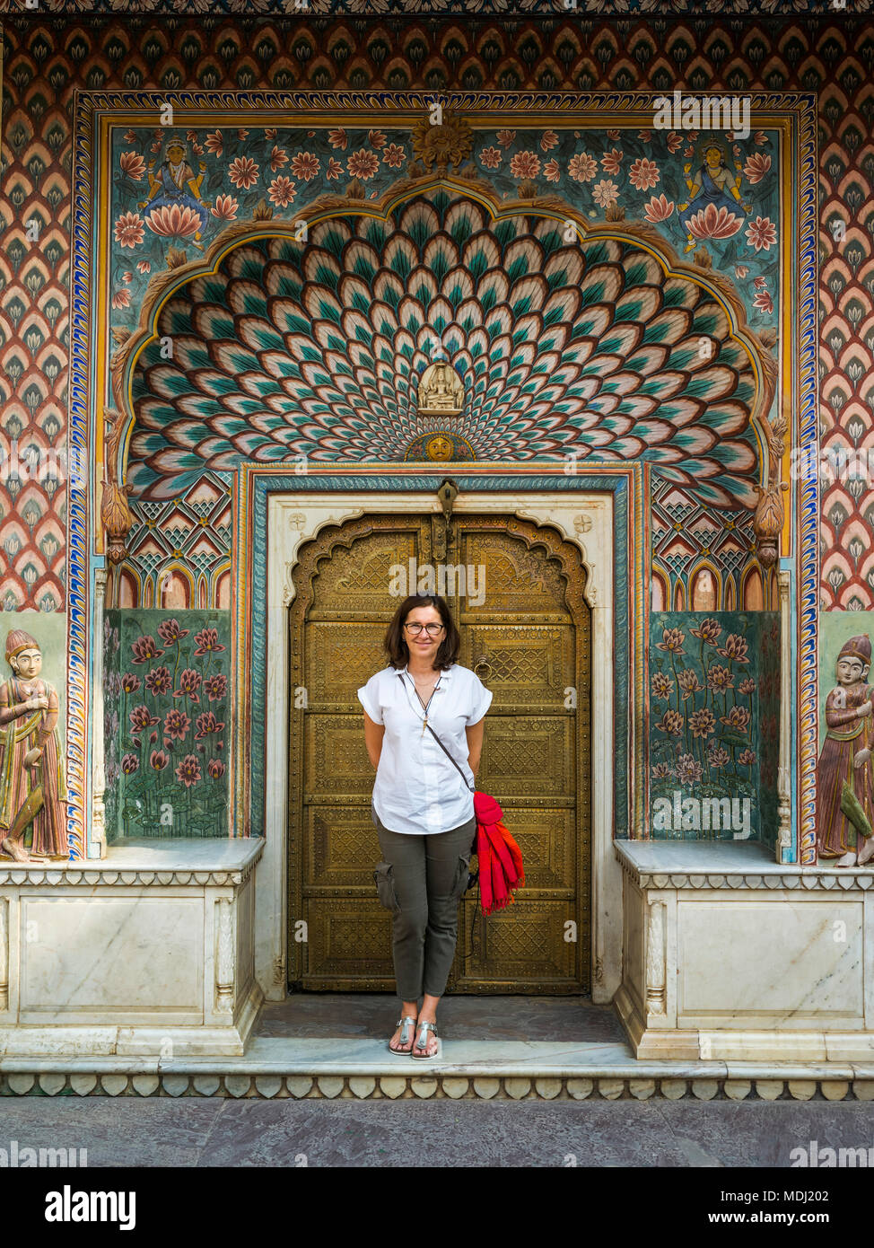A female tourist stands in front of the Peacock Gate, City Palace; Jaipur, Rajasthan, India - Stock Image