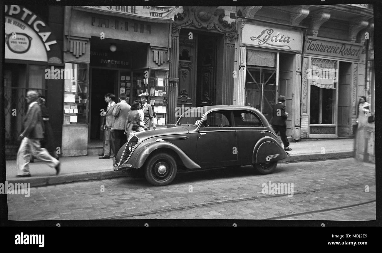 Parked on a street in France 1948 a Peugeot 202 Berline. The 202 was instantly recognizable as a Peugeot from the way that the headlights were set behind the front grille. This four-door berline (saloon) version came with a steel-panel sliding sun roof. In 1948 the wheels were embellished with chrome plated hub caps. Image from original camera B&W negative 2.5 x 4.25 inch - Stock Image