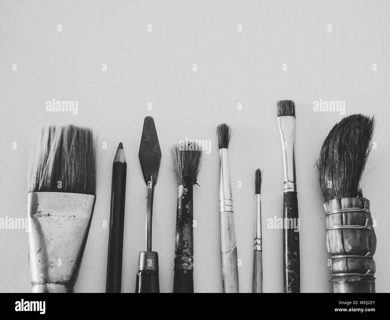 Art tools brush painting trowel and pencil on canvas