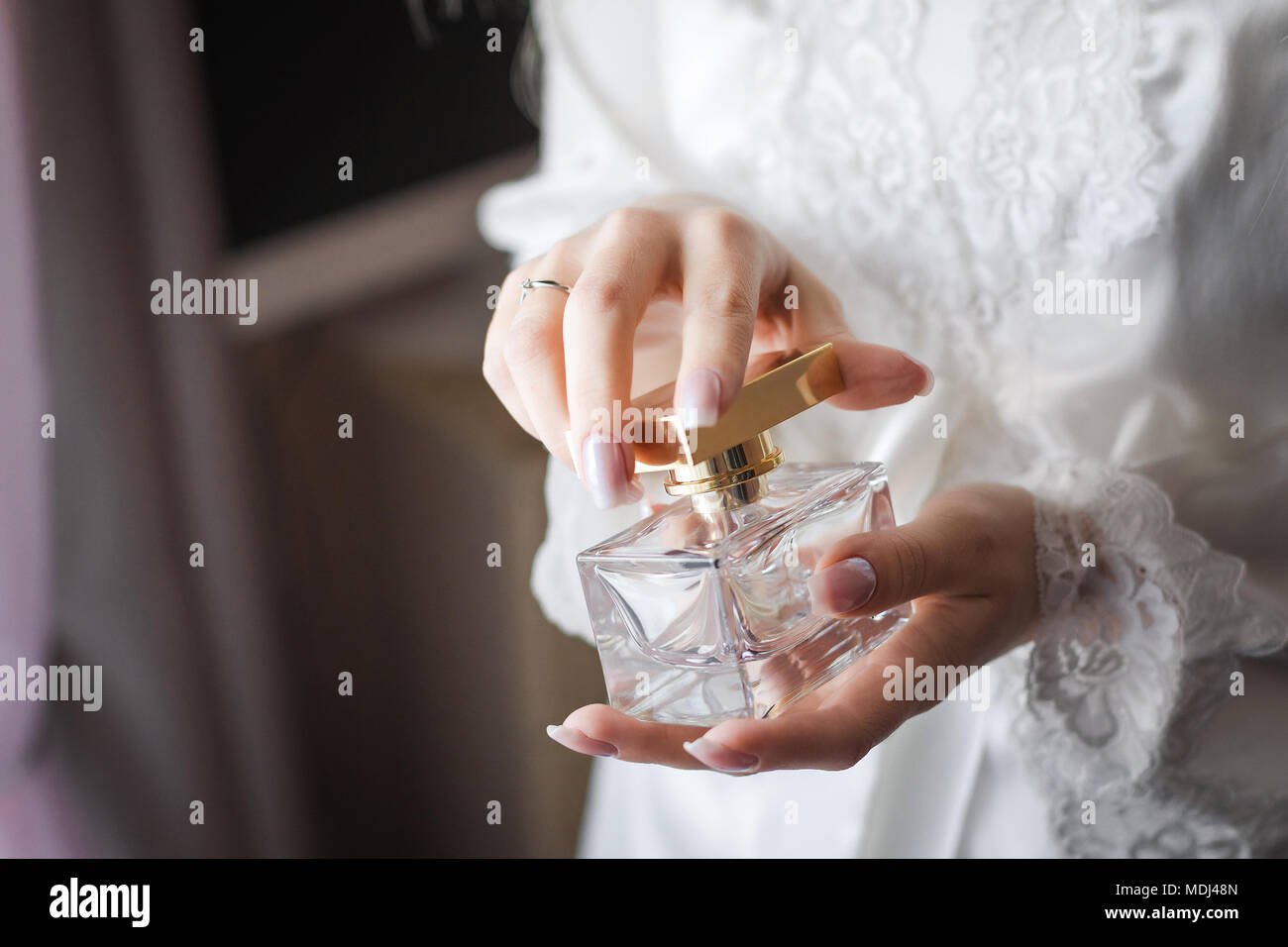 bride opening a flacon of a fragrant perfume - Stock Image