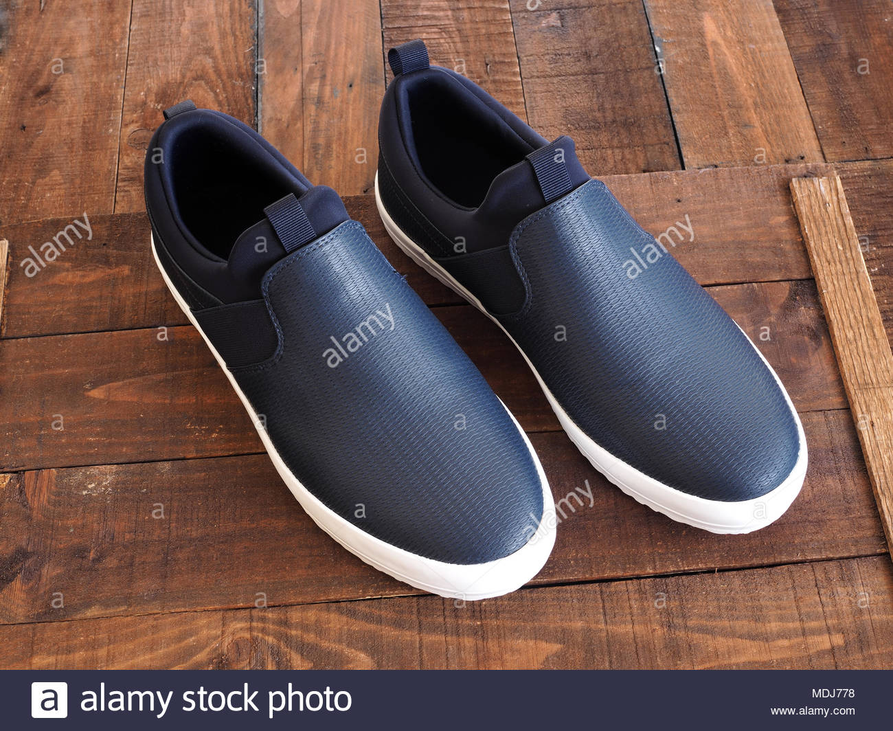 Men's dark blue slip on casual shoes, on dark wooden background - Stock Image