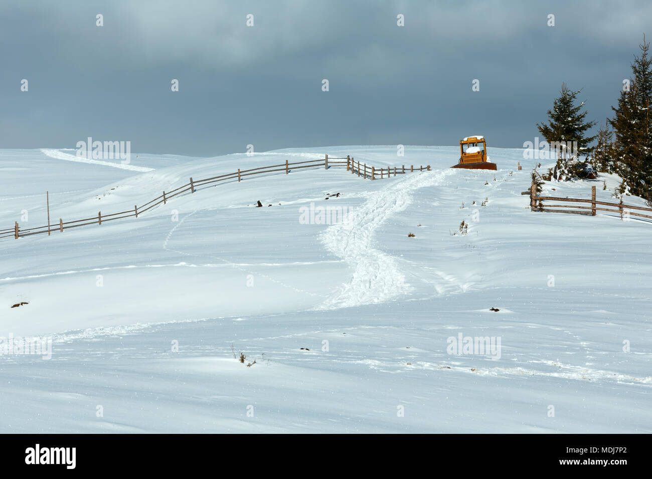 Winter  morning scenery picturesque mountain rural snow covered path and blocked by snow bulldozer on hill top (Ukraine, Carpathian Mountains, tranqui - Stock Image