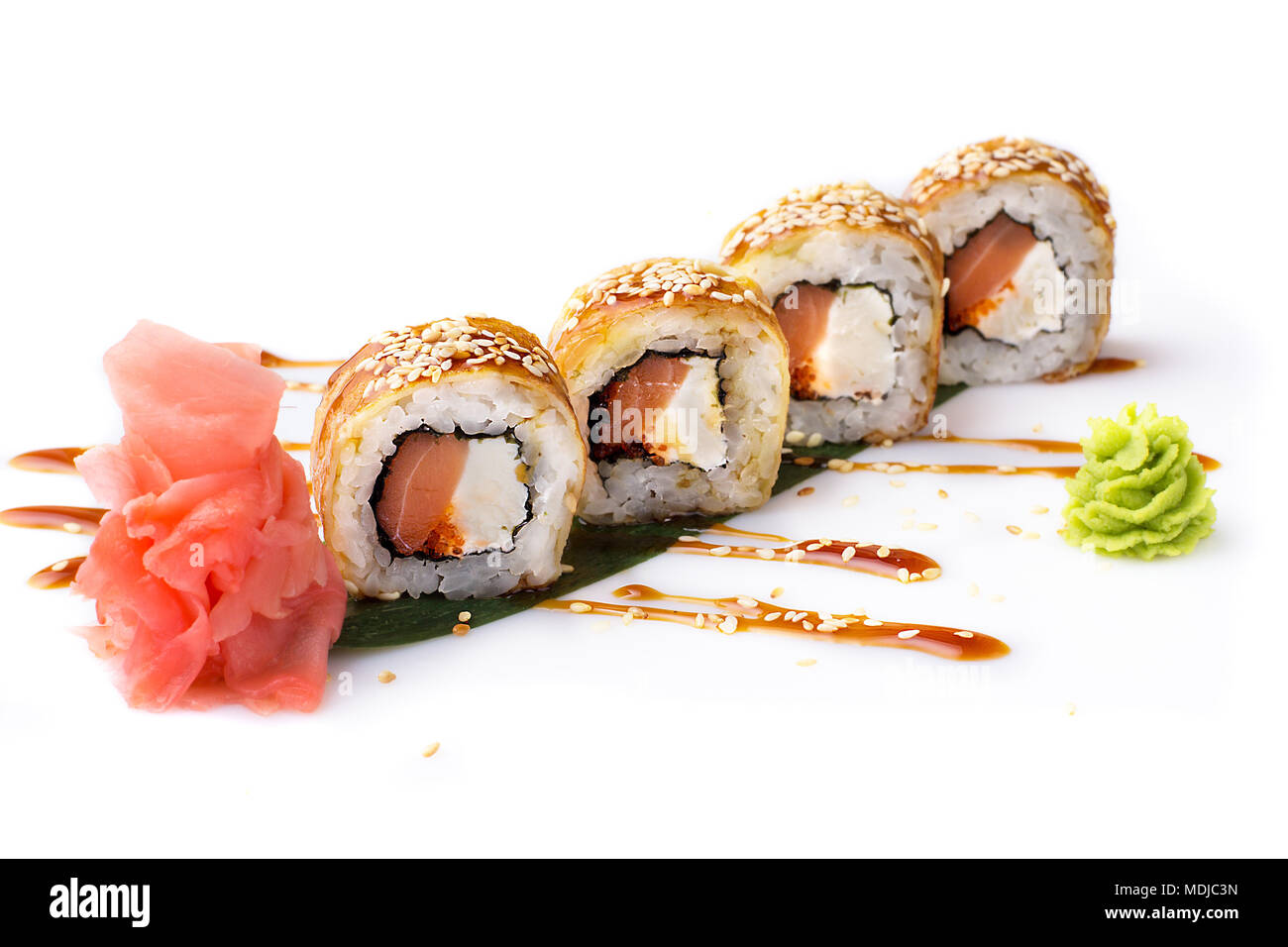 Appetizing and original sushi rolls with smoked salmon and Philadelphia cheese in an omelette laid out on a banana leaf. Isolated. Sushi roll on a whi Stock Photo
