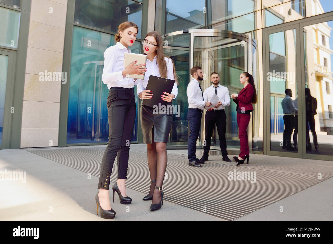 Business lady. Office staff. Two young girls with electronic tablets communicate against the background of a multi-storey glass office building and a  - Stock Image