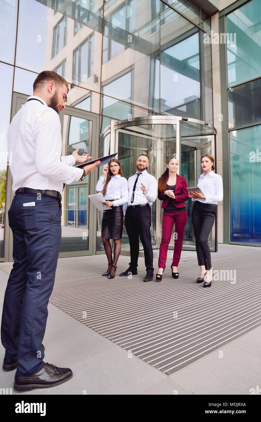 Meeting. Teamwork. The chief talks with the office staff against the background of a multi-storey office. A team of young employees are engaged in a d - Stock Image