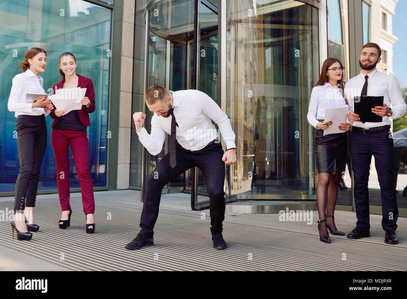 A young male businessman is enjoying a successful deal on the background of office workers. Demonstration of positive emotions and gestures. Career. S - Stock Image