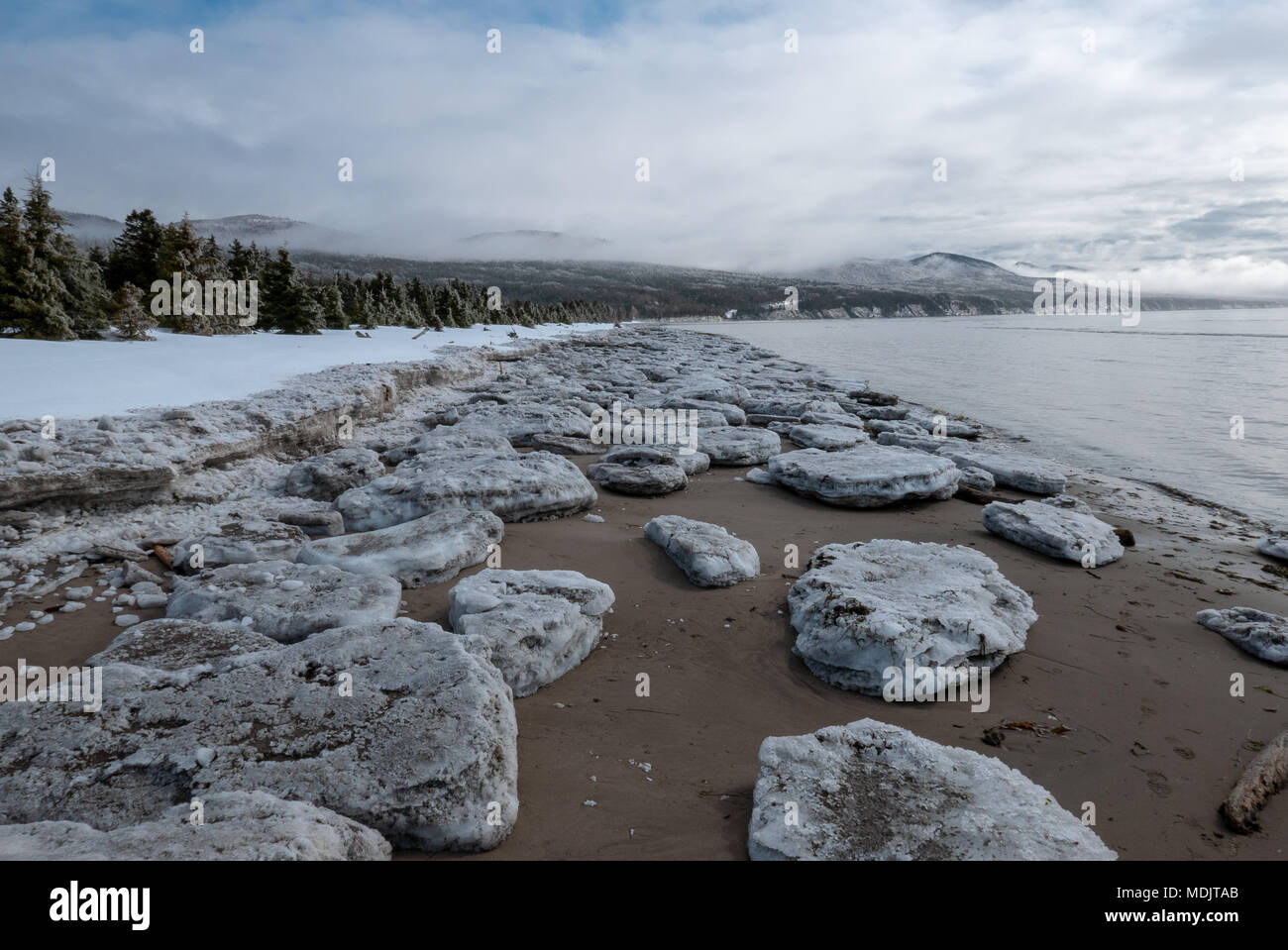 Coastal beach scenery with sea ice breakup during spring thaw. - Stock Image