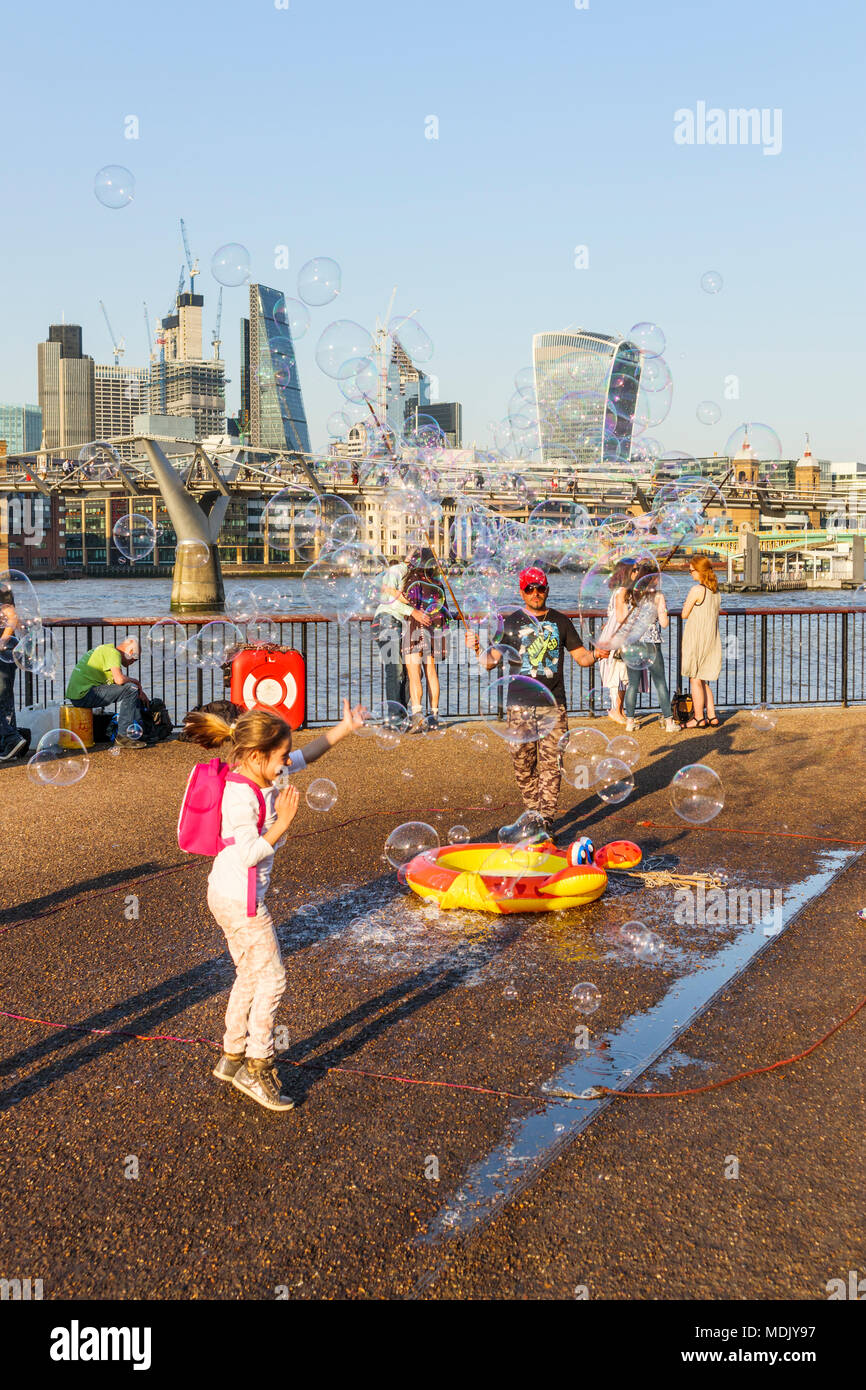 London, UK, 19th April, 2018. An entertainer on the south bank of the Embankment of the River Thames at Bankside blows bubbles to entertain children against a skyline background of iconic modern skyscraper buildings in the City of London. The sunny fine weather on the warmest April day in decades brought out good-natured crowds to enjoy the sunshine. Credit: Graham Prentice/Alamy Live News. - Stock Image