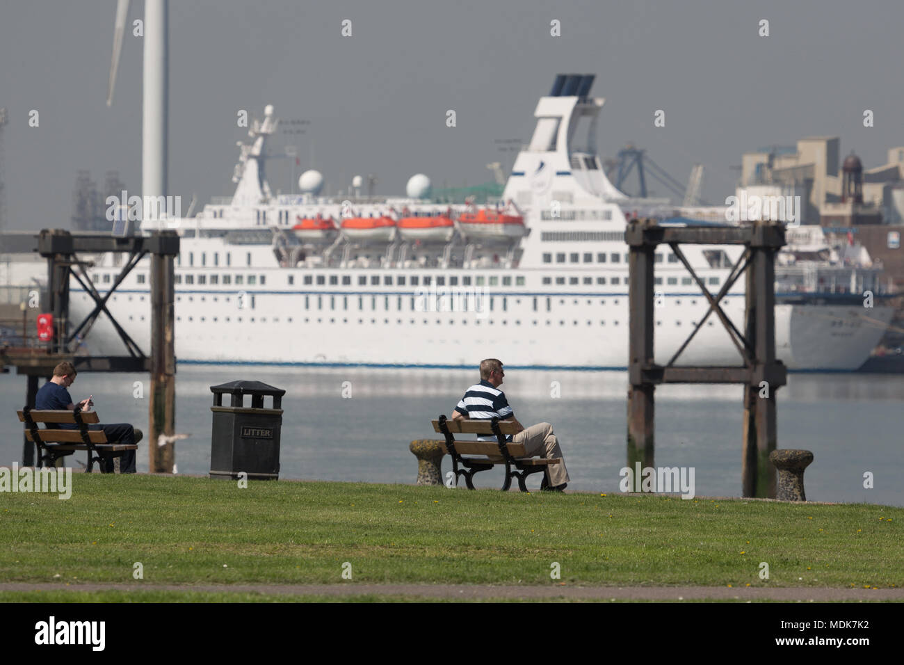 Gravesend, United Kingdom. 20th April, 2018. People relax at Gravesend Prom with cruise ship Astor pictured across the Thames at Tilbury. Gravesend in Kent is enjoying a baking hot day with high temperatures and bright sunshine. Gravesend often records the highest temperature of anywhere in the country. Rob Powell/Alamy Live News - Stock Image