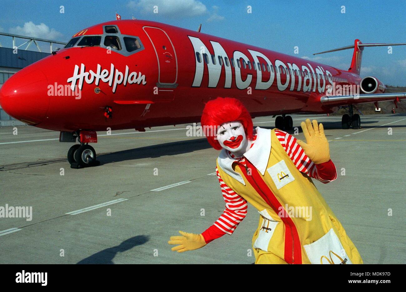 Ronald McDonald, clown of the American fast food chain McDonald's, presents the world's first Jet with McDonald's livery at the airport Basel/Mulhouse on 29.03.1996. The bright red McDonnell Douglas MD-83 with the white lettering of the fast food chain is used from 01.04.1996 by the Swiss Crossair (Swissair subsidiary) in the European holiday charter traffic. The Swiss tour operator Hotelplan participates in the company.   usage worldwide - Stock Image