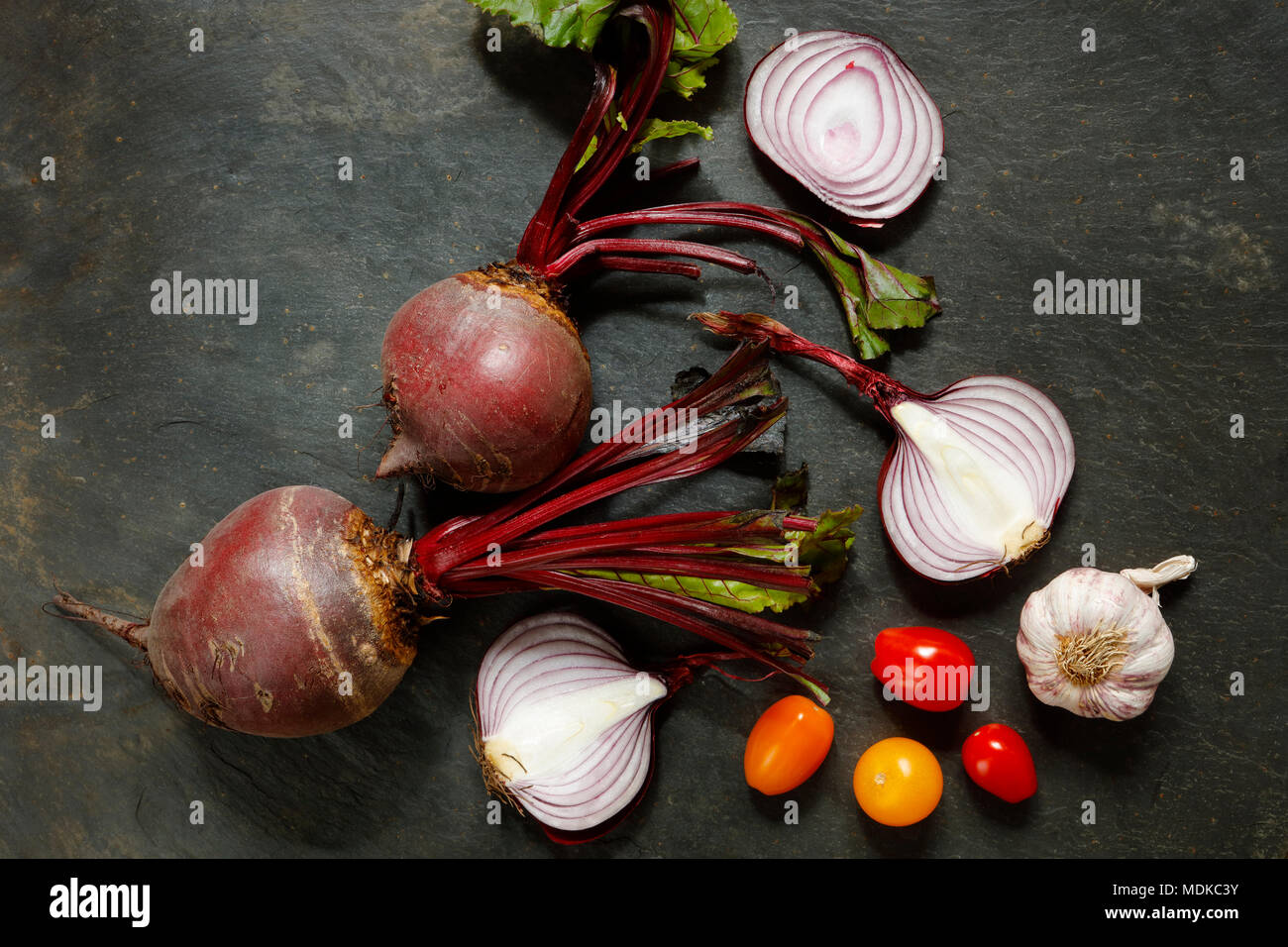 Fresh whole  beetroot with red onions , garlic and cherry tomatoes on slate table with copy space - Stock Image
