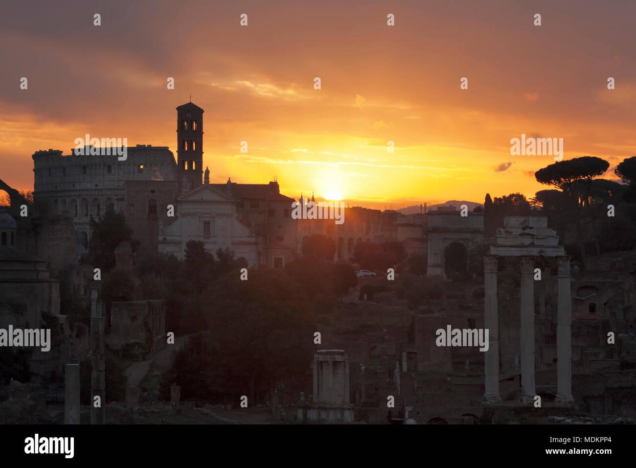 View over the Roman Forum to the Colosseum at sunrise, Foro Romano, Rome, Lazio, Italy - Stock Image