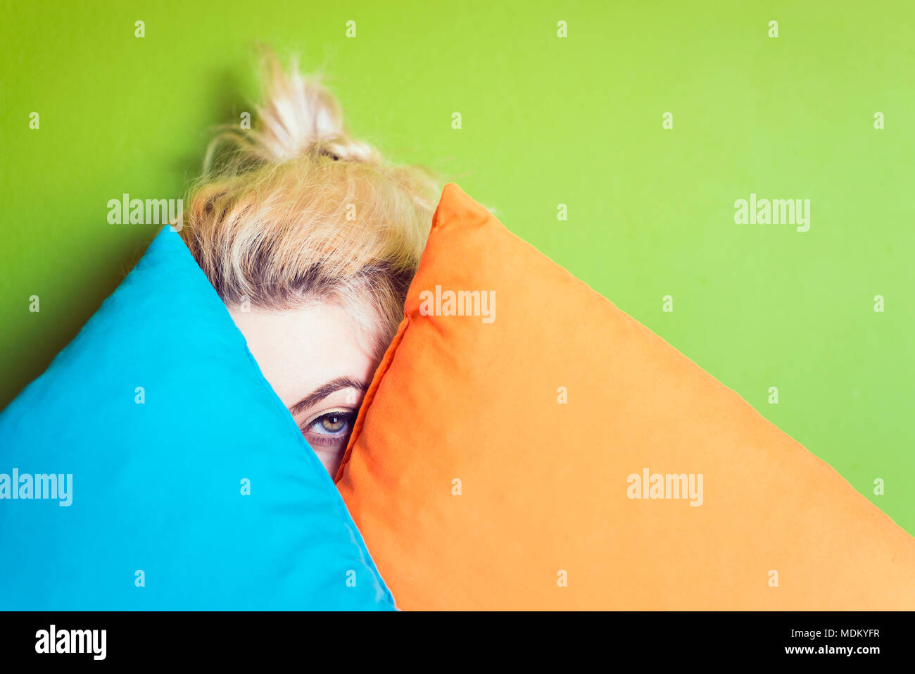 Young woman hiding behind colorful cushions - Stock Image
