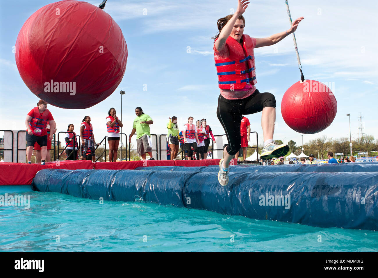 A woman slips and falls into the water running through the wrecking balls event, at the Ridiculous Obstacle Course on April 5, 2014 in Atlanta, GA. - Stock Image