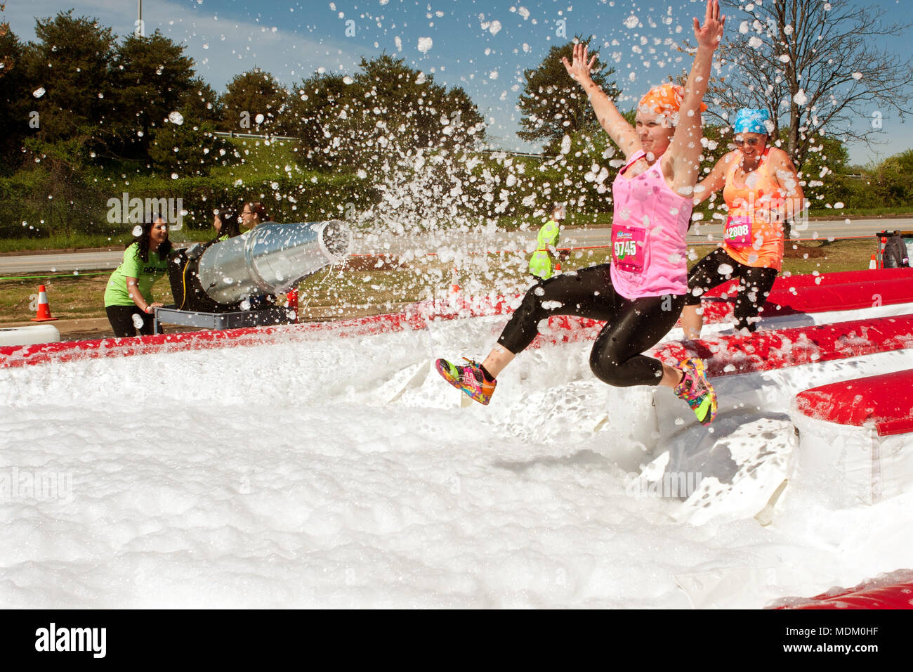 Young women get sprayed with bubbles jumping into a foam pit, as they take part in the Ridiculous Obstacle Challenge on April 5, 2014 in Atlanta, GA. - Stock Image