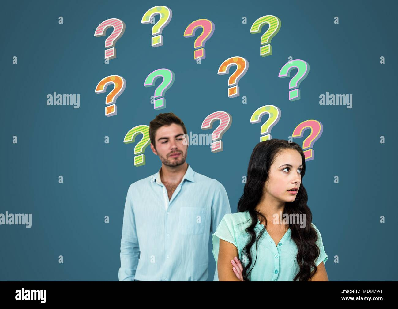Confused unhappy couple with colorful funky question marks - Stock Image