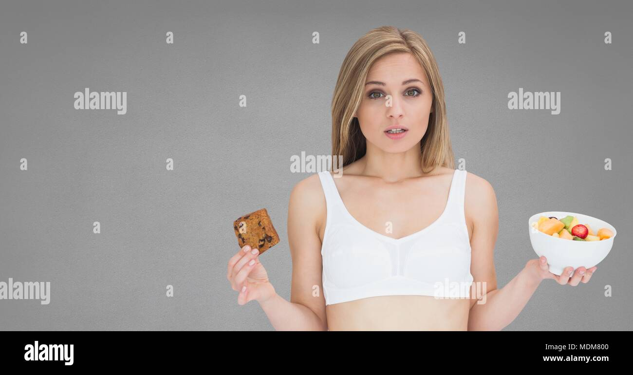Woman holding deciding healthy and unhealthy food choice - Stock Image