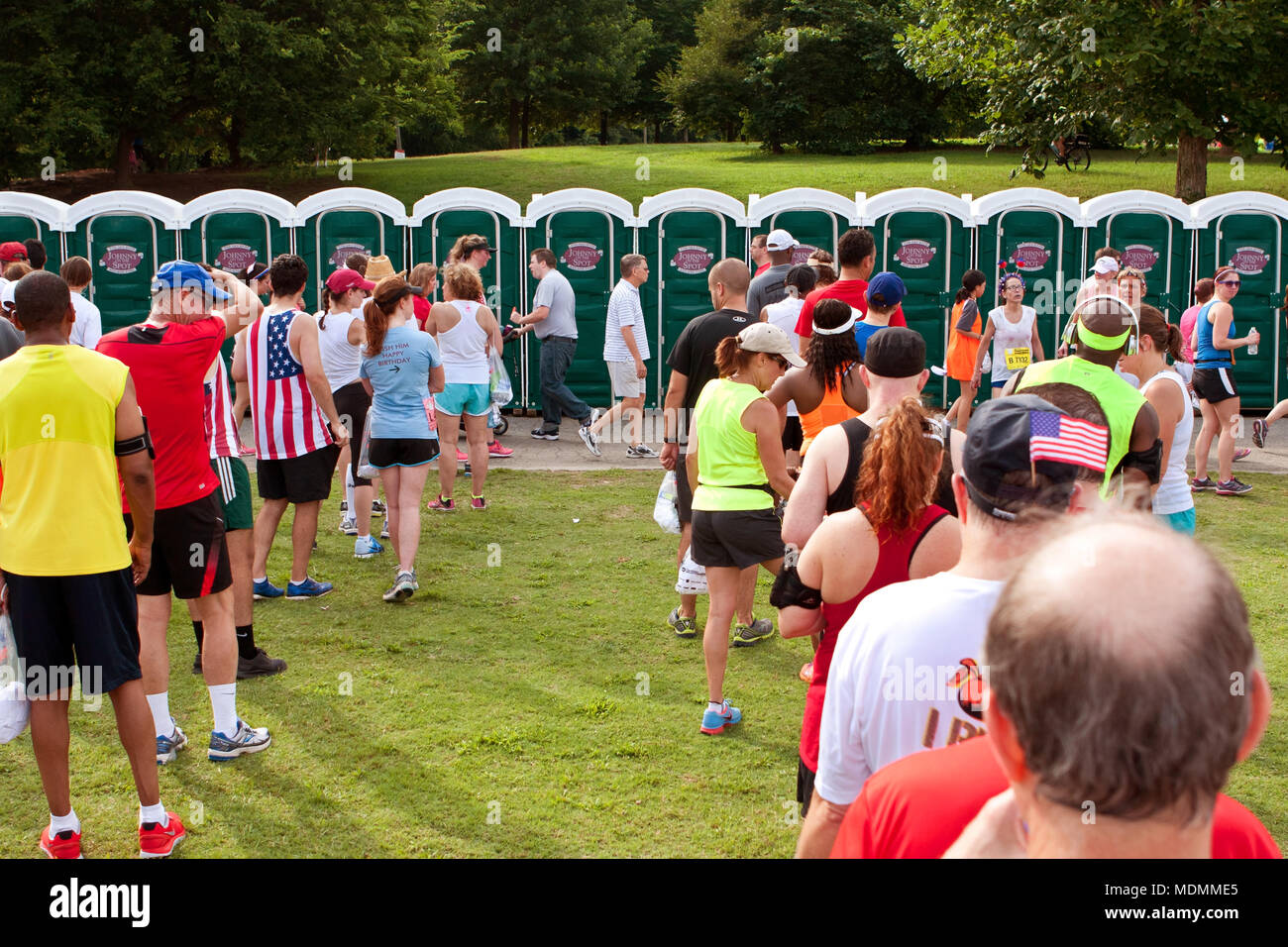 Exhausted runners wait in long lines to use a Johnny On The Spot portable toilet, at the Peachtree Road Race on July 4, 2014 in Atlanta, GA. - Stock Image