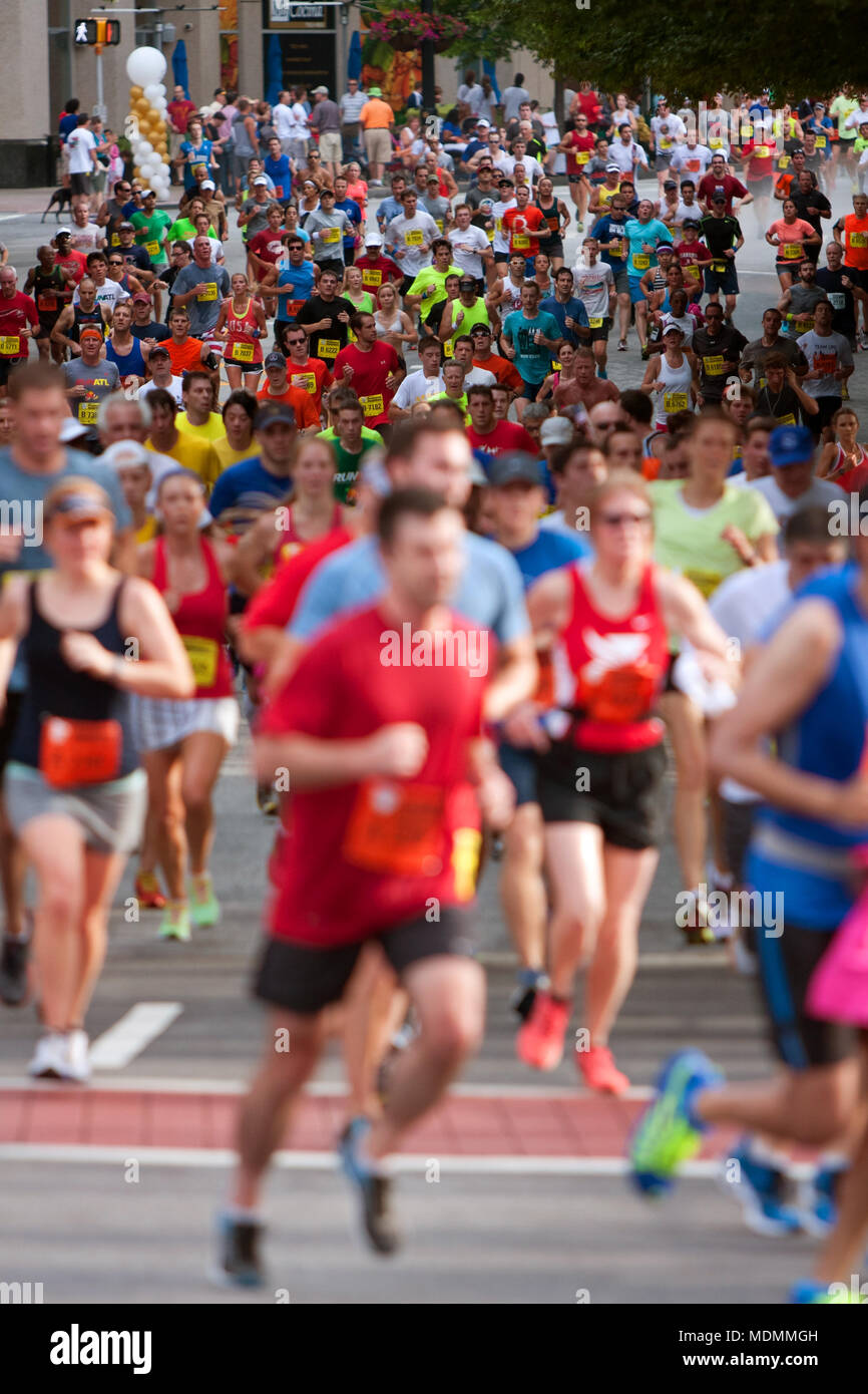 Thousands of runners make their way down Peachtree Street on their way to the finish line of the Peachtree Road Race on July 4, 2014 in Atlanta, GA. - Stock Image