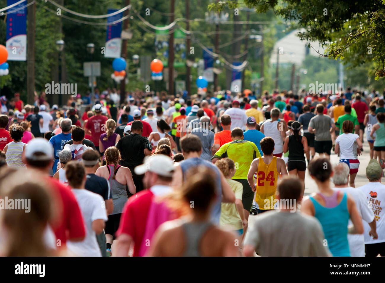 Atlanta, GA, USA - July 4, 2014:  Thousands of runners crowd an Atlanta street on their way to the finish line of the Peachtree Road Race. - Stock Image