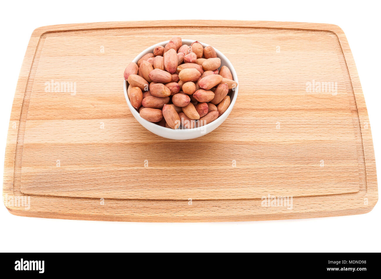 Mixed nuts in a metal brown bowl on a white wooden cutting board. - Stock Image