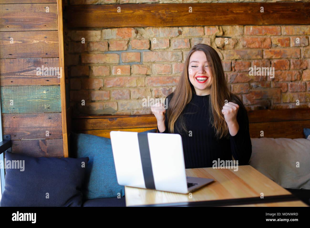 Fortunate girl enjoying winning betting online by laptop at cafe. - Stock Image
