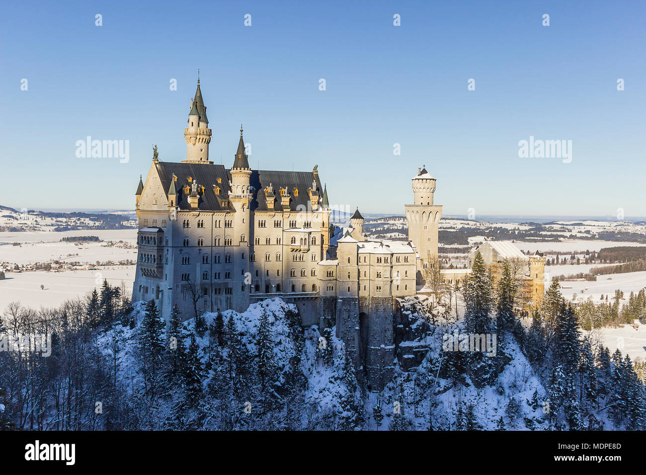 View of Neuschwanstein Castle from  Queen Mary's Bridge surrounded by trees and snow - Stock Image