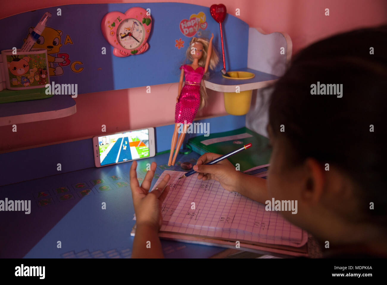 Little girl watching videos on smartphone while studying. - Stock Image
