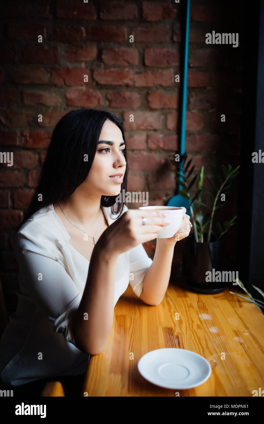 Young woman drinking coffee in a cafe outdoors. - Stock Image