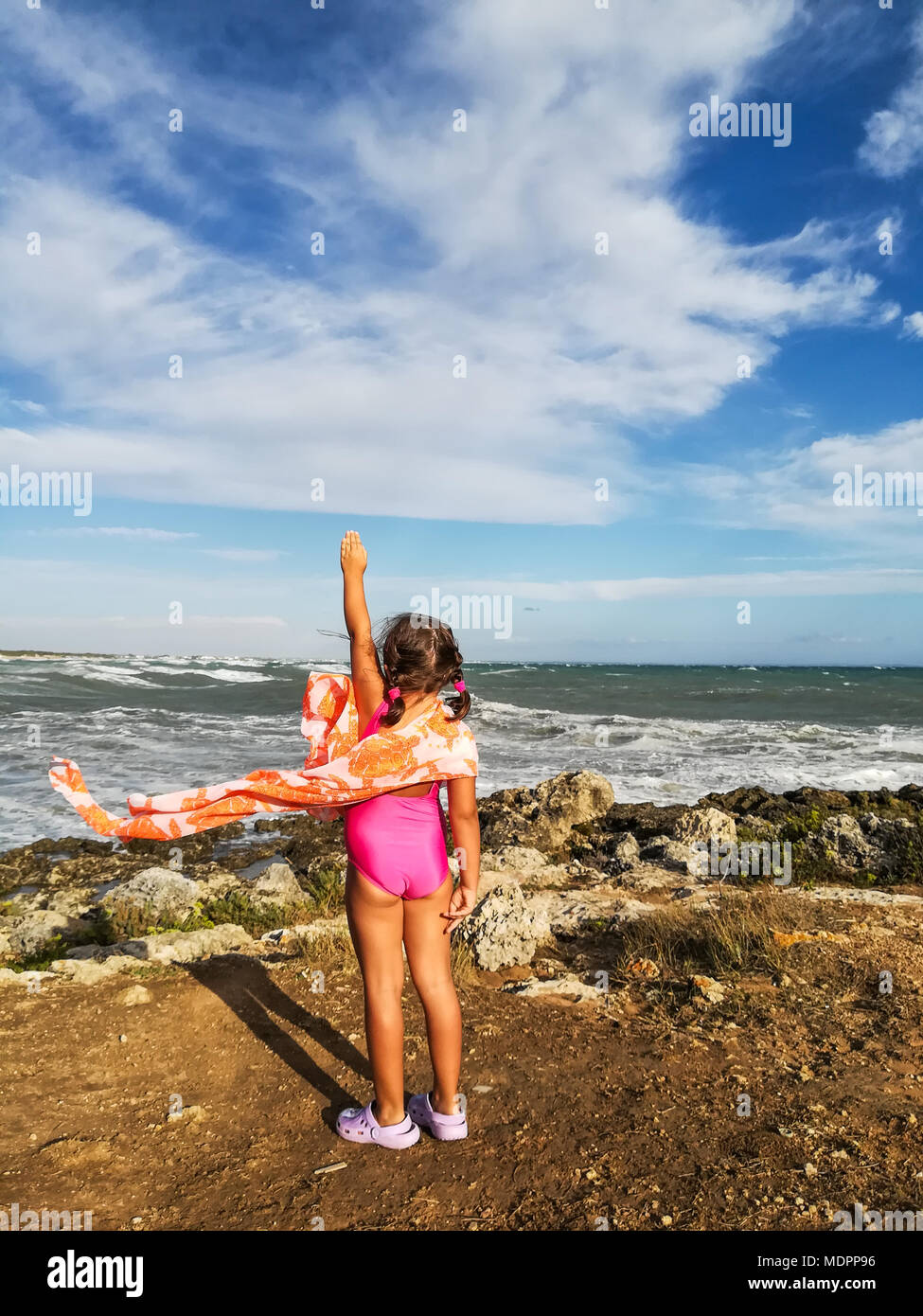 A little 'supergirl' in front of sea. - Stock Image