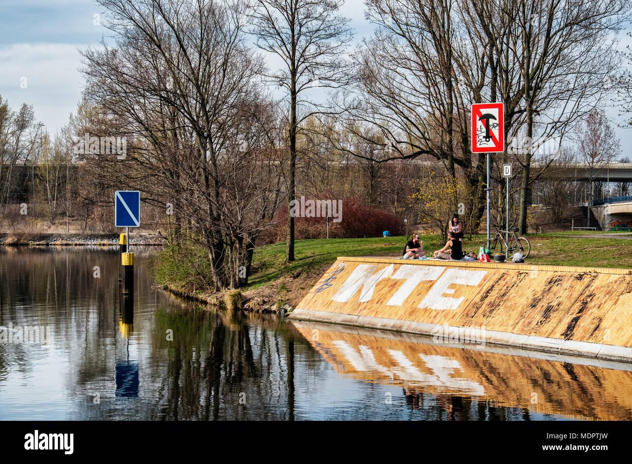 Berlin Charlottenburg-Wilmersdorf, Three young people picnic in park next to Schleusenkanal n Spring - Stock Image