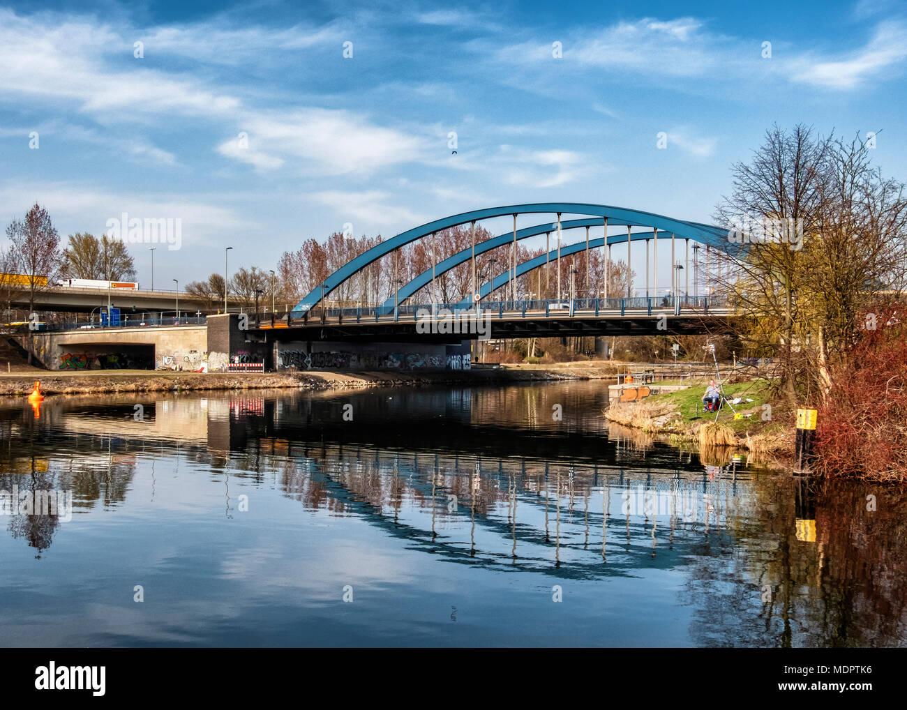 Berlin Charlottenburg-Wilmersdorf. Mörschbrücke. steel tied-arch road bridge over the Westhafen canal & man fishing Stock Photo