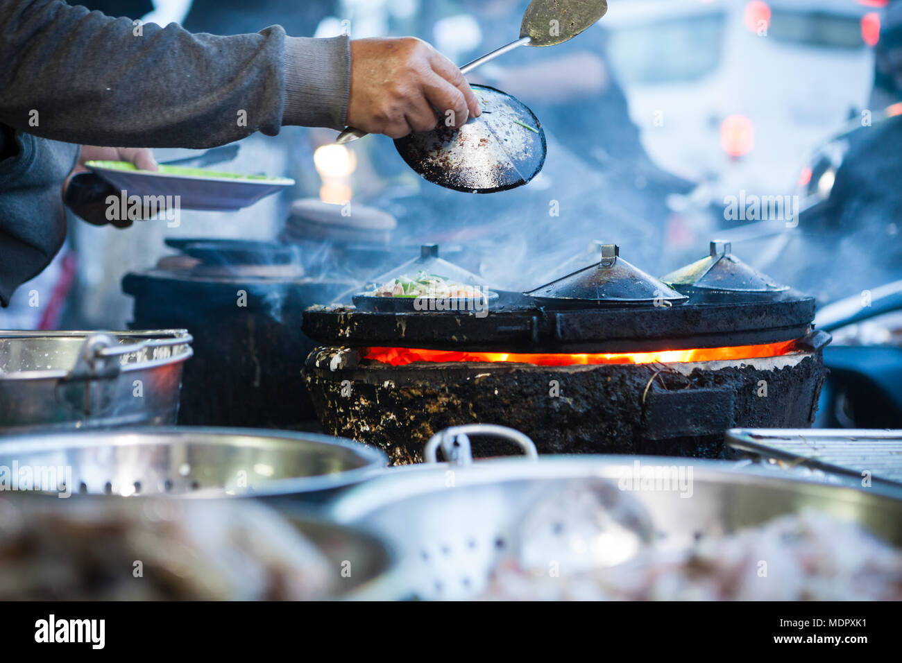 Nha Trang, Vietnam - march 16 2017: street food, cooking  banh xeo - savoury rice-flour pancakes with shrimp and bean sprouts - Stock Image