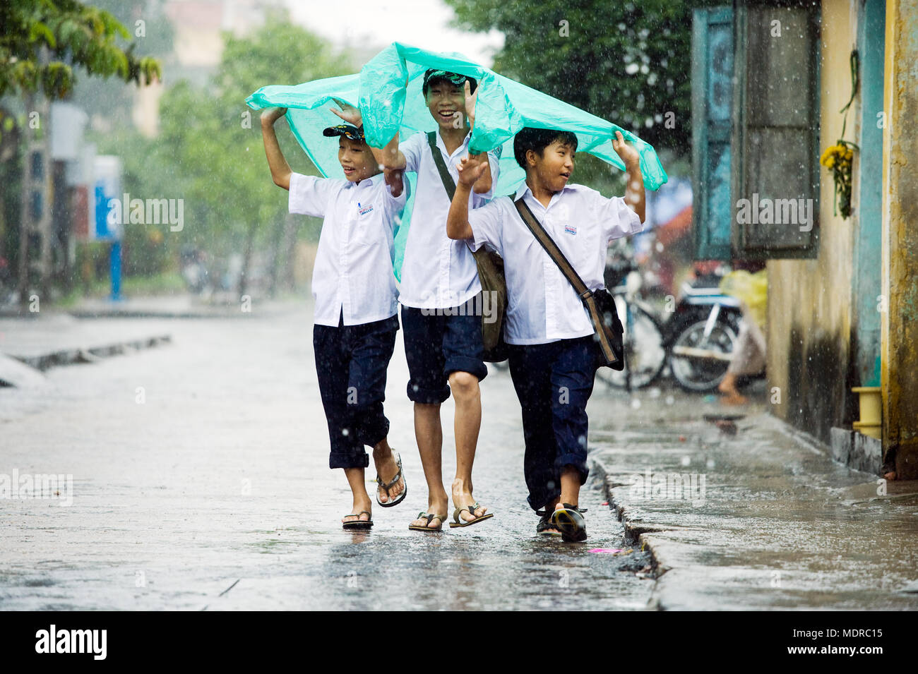 Hoi An, Vietnam; boys sheltering from a downpour in the rainy season - Stock Image