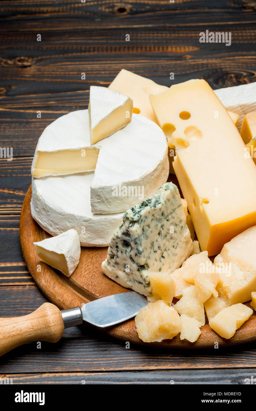 various types of cheese - brie, camembert, roquefort and cheddar on wooden board - Stock Image