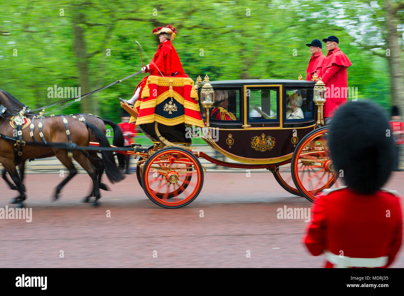 LONDON - MAY 18, 2016: A horse-drawn royal carriage passes in front of a guard from the household calvary on The Mall. - Stock Image
