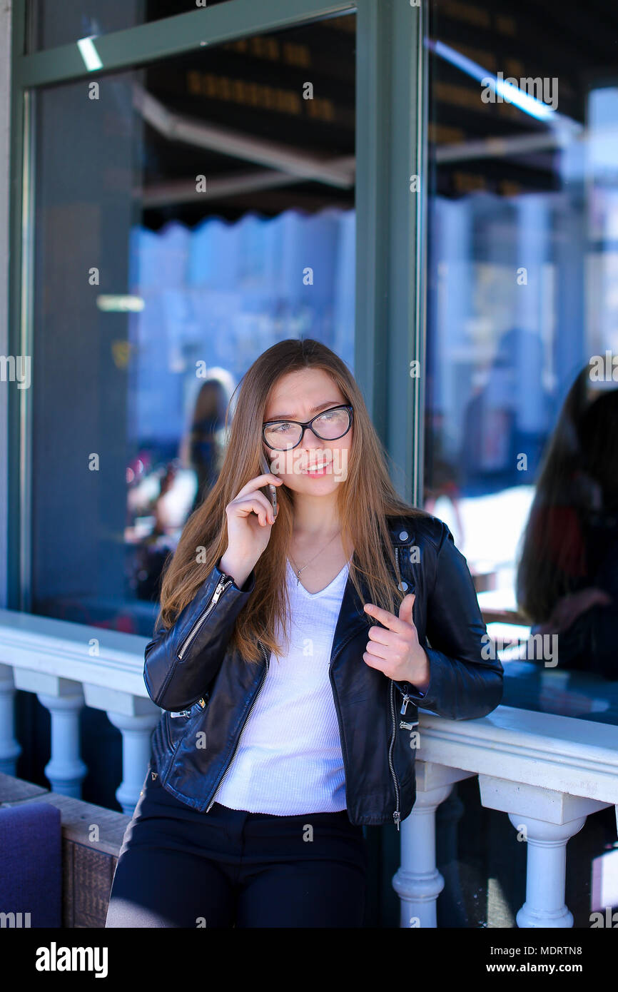 Nice woman in glasses speaking by smartphone at street cafe. - Stock Image