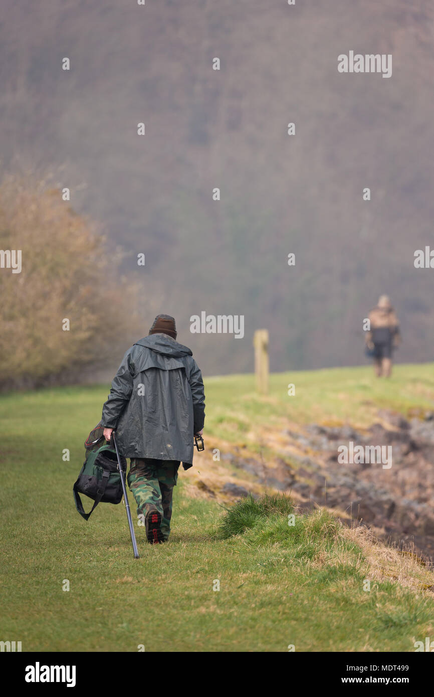 Rear view of fisherman in waterproofs, with tackle, walking by water's edge in pursuit of more successful fishing peg. Companion angler in background. - Stock Image