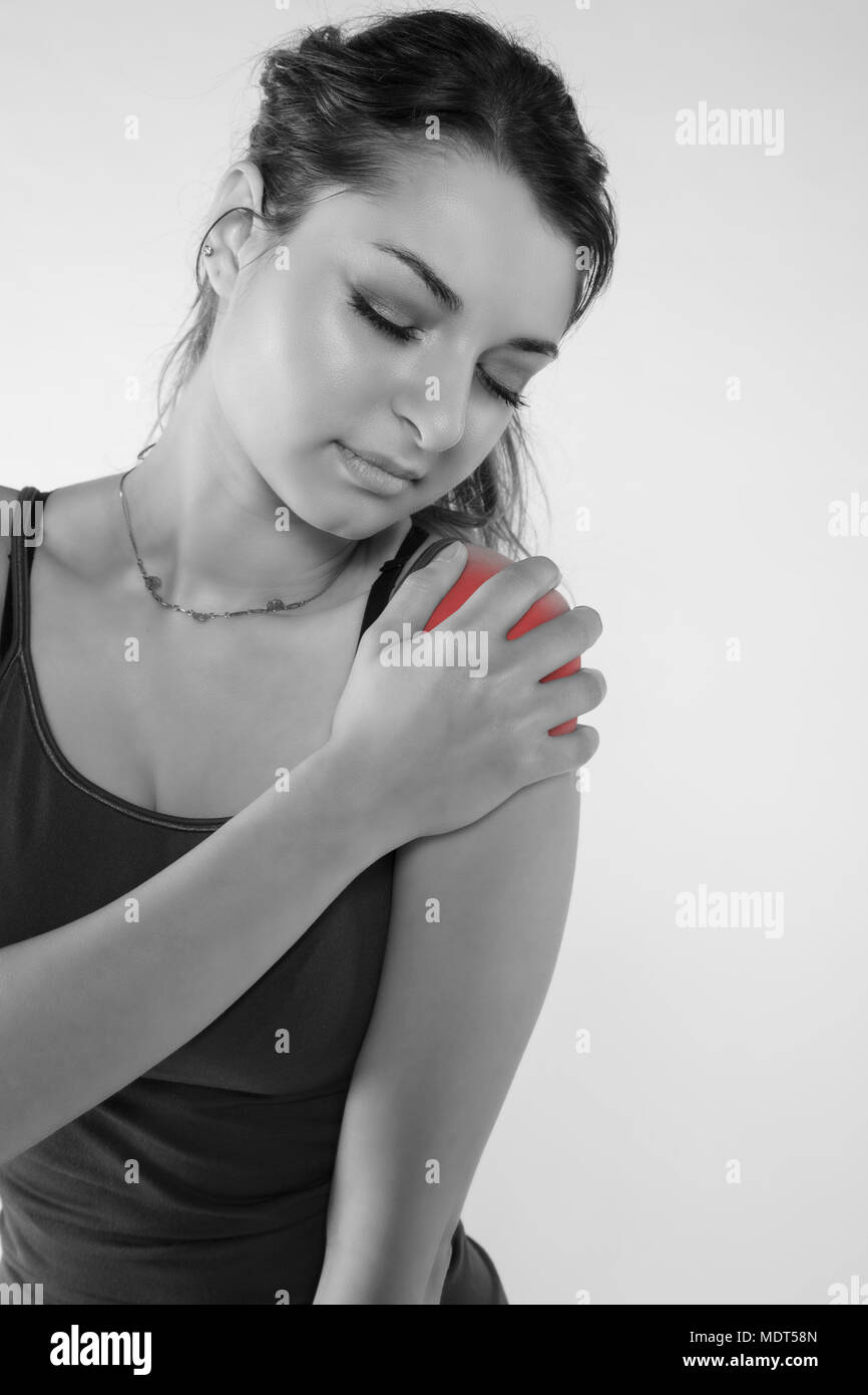 A young woman is struggling with pain, isolated on background - Stock Image