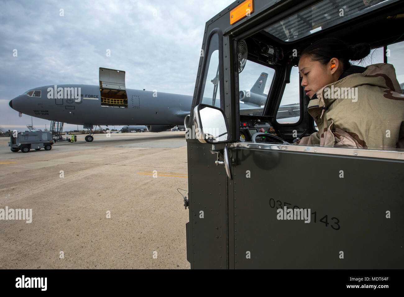 U.S. Air Force Senior Airman Vince Tsang, an Aerial Porter with the 88th Aerial Port Squadron, 514th Air Mobility Wing, checks the rear view mirror of a K-loader while in Mission Oriented Protective Posture level two gear during a KC-10 Extender cargo loading exercise at Joint Base McGuire-Dix-Lakehurst, N.J., Dec. 3, 2017.  (U.S. Air Force photo by Master Sgt. Mark C. Olsen) - Stock Image