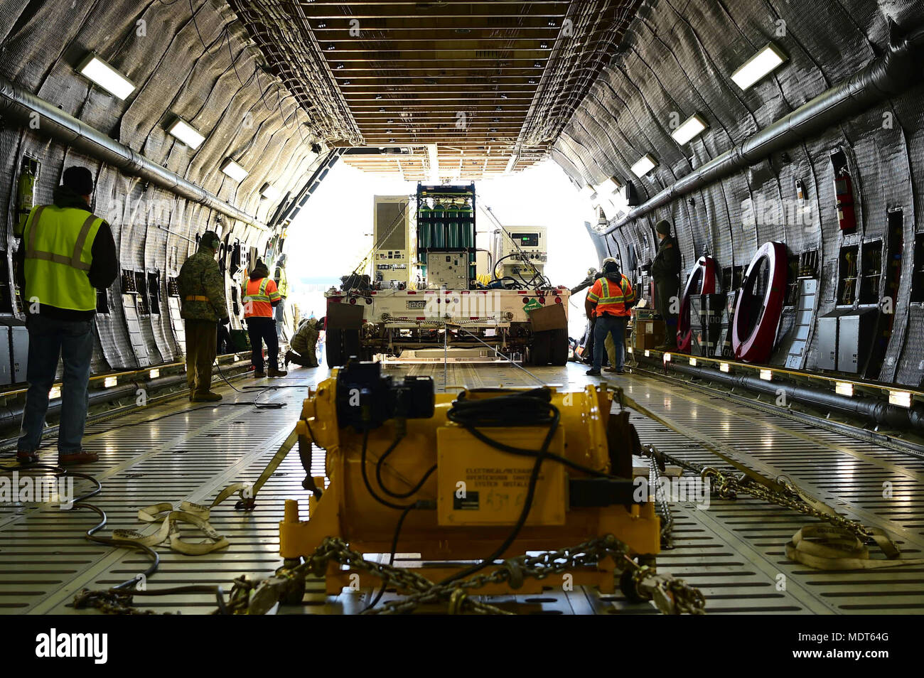 Personnel assisting with the loading of the Geostationary Operational Environmental Satellite – R Series into a C-5 Galaxy aircraft make sure the load is properly aligned before using the wench to pull it into the body of the aircraft Dec. 4, 2017, on Buckley Air Force Base, Colorado. A heavy duty wench capable of pulling well over 100 thousand pounds was used to tow the payload into a C-5 Galaxy for transport down to Cape Canaveral, Florida. (U.S. Air Force photo by Senior Airman Luke W. Nowakowski) - Stock Image