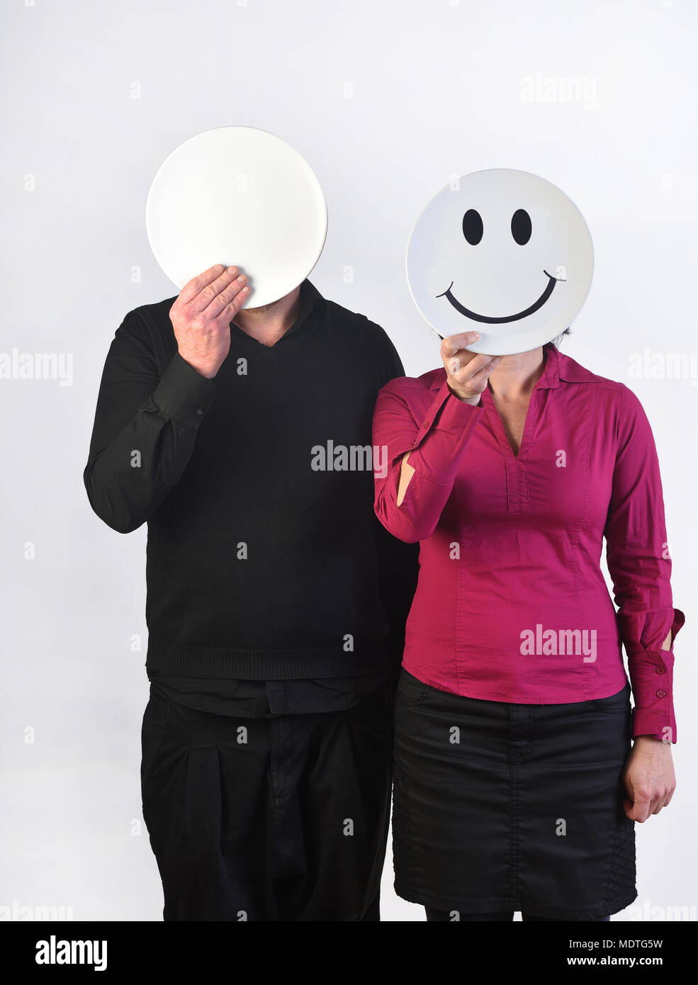 a happy woman and a deadpan man - Stock Image