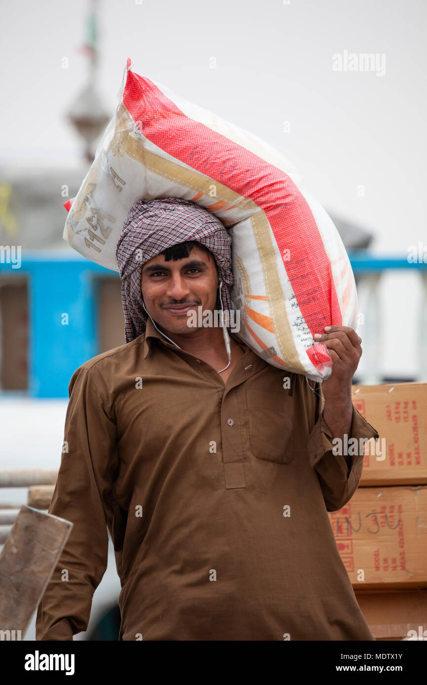 Labourer unloading sacks from a dhow moored along the Dubai Creek, Deira, Dubai, United Arab Emirates, Middle East Stock Photo