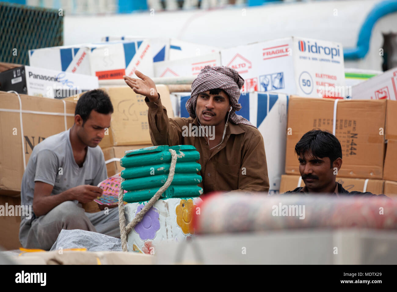 Labourers taking a break from work unloading from a dhow moored along the Dubai Creek, Deira, Dubai, United Arab Emirates, Middle East - Stock Image