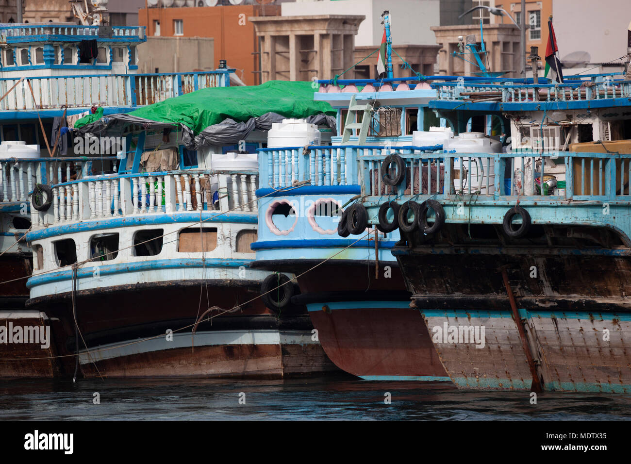 Blue sterns of dhows mooored along the Dubai Creek, Deira, Dubai, United Arab Emirates, Middle East - Stock Image