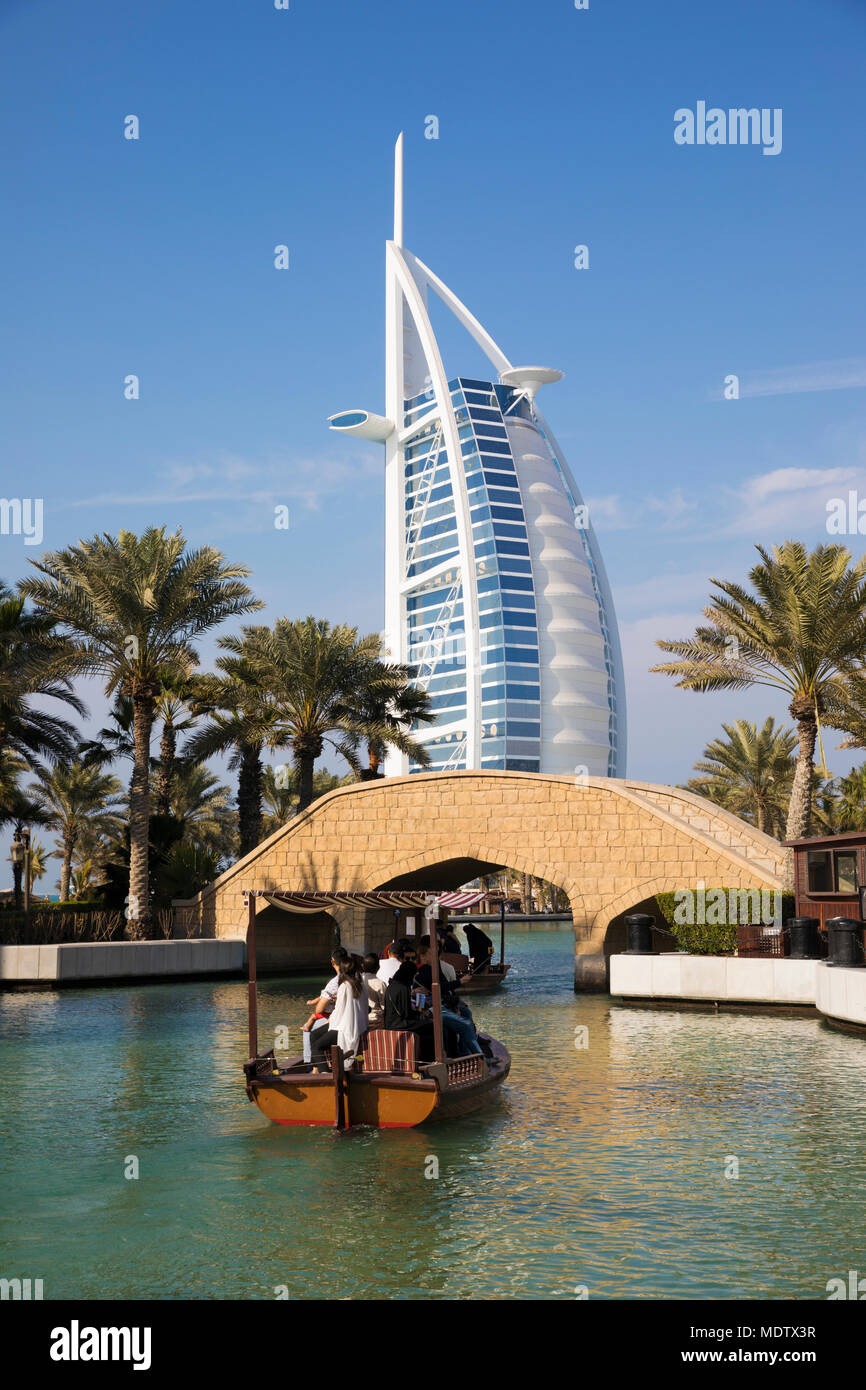 Tourists riding on an abra on the waterways of the Madinat Jumeirah with the Burj Al Arab behind, Dubai, United Arab Emirates, Middle East - Stock Image
