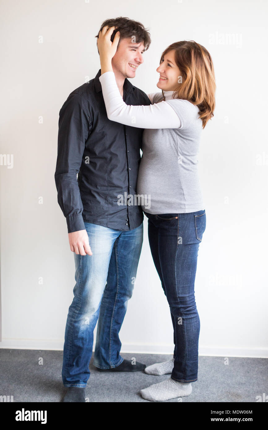 happiness, harmony, relationships concept. there is happy newly married couple, she is pregnant, and her husband is delicately hugging her with one hand - Stock Image