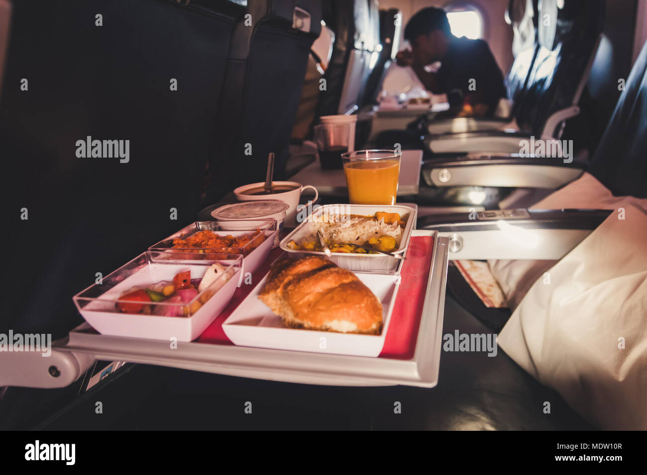 Tray of food. The passenger eats food on Board the plane on the background of the window. Meals on the plane. Different sets of food on the folding ta - Stock Image
